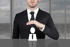 Businessman holding protective hand above employee Stock Photography