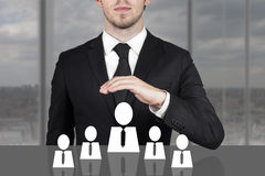 Businessman holding protective hand above employee staff. Businessman in black suit holding protective hand above employee staff Stock Photo