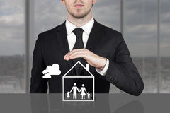 Businessman holding protective hand above family home. Businessman in black suit holding protective hand above family home royalty free stock image