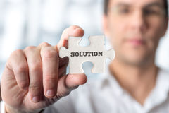 Businessman holding puzzle piece with word Solution Royalty Free Stock Images