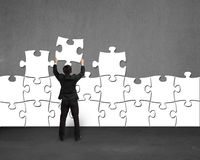 Businessman holding puzzle to assemble on concrete wall Royalty Free Stock Images