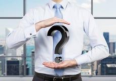 Businessman holding question mark. Businessman holding black question mark, close up Royalty Free Stock Photo