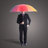 Businessman holding rainbow umbrella Stock Images
