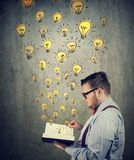 Businessman holding reading an opened book with glowing light bulbs flying out royalty free stock photography