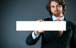 Businessman holding a rectangular blank sign Stock Photo