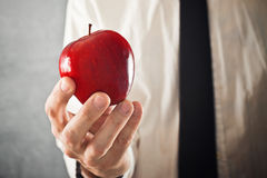 Businessman holding red apple Stock Photo