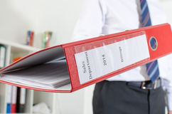 Businessman holding a red binder. At office Stock Image