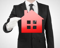 Businessman holding red house Royalty Free Stock Images