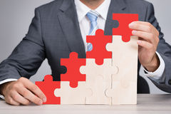 Businessman Holding Red Jigsaw Graph On Table Stock Photo