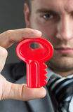 Businessman holding red toy key Royalty Free Stock Photos