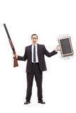 Businessman holding rifle and a bag full of money Royalty Free Stock Images
