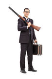 Businessman holding a rifle and a briefcase Royalty Free Stock Photos