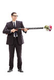 Businessman holding a rifle loaded with flowers Royalty Free Stock Photography
