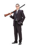 Businessman holding a rifle over his shoulder Stock Photos
