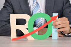 Businessman holding roi with upward moving arrow Royalty Free Stock Image