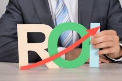 Businessman holding roi with upward moving arrow. Midsection of businessman holding ROI (return on investment) with upward moving arrow at table Royalty Free Stock Image