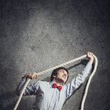 Businessman holding rope Stock Photography