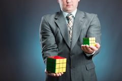 Businessman holding rubik cube in his hands Stock Image