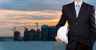 Businessman holding safety helmet with city background Stock Photo
