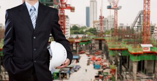 Businessman holding safety helmet with construction site in back Stock Photography