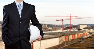 Businessman holding safety helmet with construction site Stock Images