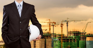 Businessman holding safety helmet with construction site Stock Image