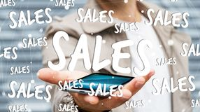 Businessman holding sales icons over his phone 3D rendering. Businessman on blurred background holding sales icons over his phone 3D rendering Royalty Free Stock Image