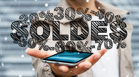 Businessman holding sales icons over his phone 3D rendering. Businessman on blurred background holding sales icons over his phone 3D rendering Royalty Free Stock Photo