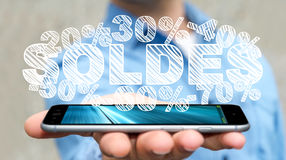 Businessman holding sales icons over his phone 3D rendering. Businessman on blurred background holding sales icons over his phone 3D rendering Stock Photos