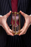 Businessman holding a sand timer. Close up shot of a businessman holding a brass sand timer or hourglass Royalty Free Stock Photos