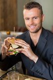 Businessman Holding Sandwich In Restaurant Stock Images