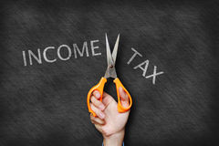Businessman holding scissor cutting income tax text on blackboar Stock Image