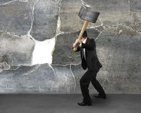 Businessman holding sedgehammer to crack wall Royalty Free Stock Photo