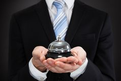 Businessman holding service bell. Midsection of businessman holding service bell against black background Stock Photography