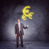 Businessman holding set of big euro signs Stock Photos