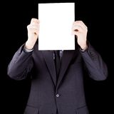 Businessman holding  a sheet of paper in front of his face Stock Photo