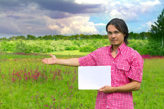 Businessman holding sheet of paper on landscape Stock Image