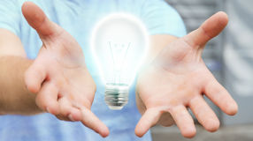 Businessman holding shiny lightbulb in his hand '3D rendering. Businessman on blurred background holding shiny lightbulb in his hand '3D rendering Stock Photos