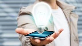 Businessman holding shiny lightbulb on mobile phone '3D render. Businessman on blurred background holding shiny lightbulb over mobile phone '3D rendering Royalty Free Stock Photo