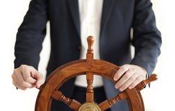 Businessman holding ship rudder isolated on white. stock photos