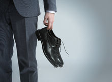 Businessman holding the shoes in hand, royalty free stock image