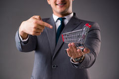 The businessman holding shopping cart in business concept Royalty Free Stock Photo