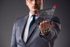 The businessman holding shopping cart in business concept. Businessman holding shopping cart in business concept Stock Photos