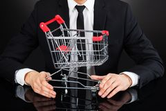 Businessman holding shopping cart model at desk Stock Photography