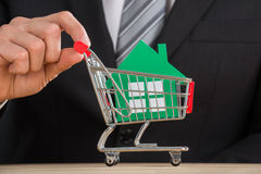 Businessman Holding Shopping Trolley With Green Paper House Stock Photo