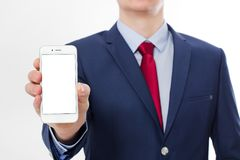 Businessman holding and showing blank screen cell phone isolated on white background. Copy space and selective focus.  stock photos
