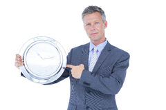 Businessman holding and showing a clock Stock Photos