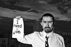 Businessman holding sign. Young businessman holding sign I need a job Royalty Free Stock Photos