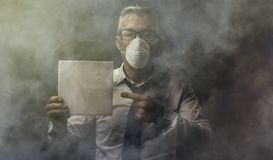 Businessman holding a sign and air pollution stock photos