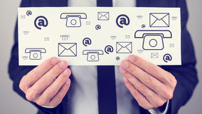 Businessman holding a sign with contact icons Royalty Free Stock Photos
